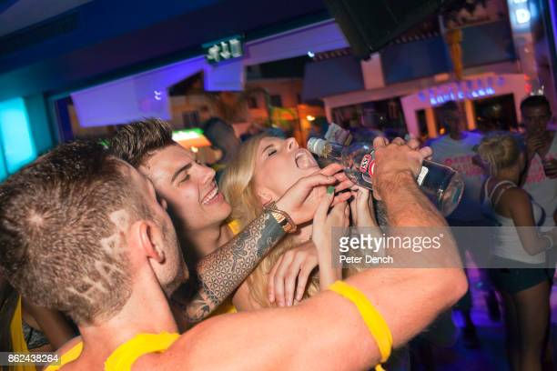 A young woman is administered some alcohol by Party Hard bar crawl staff at Ice Lounge Ayia Napa Cyprus