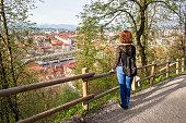 Young woman is admiring the view of Ljubljana old town from Ljubljana castle in Ljubljana, Slovenia