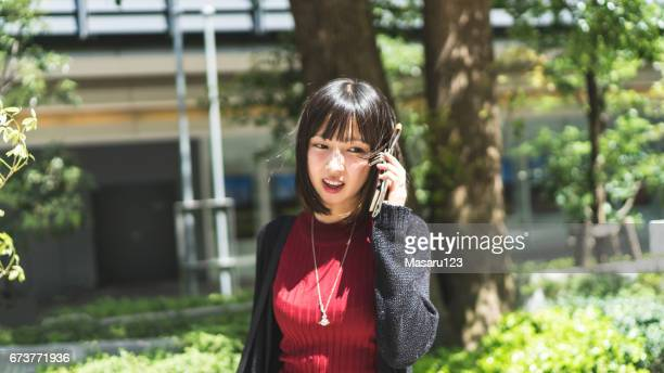 Young woman is chatting on a phone outside
