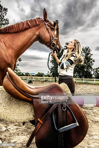 Young woman is grooming horse and preparing it for riding