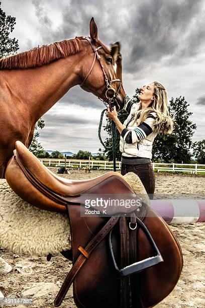 Jeune femme cheval de toilettage et la prépare à cheval