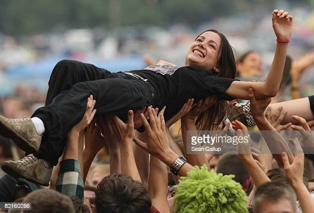 A young woman is held aloft by dancing music fans at the International Woodstock Festival on August 2 2008 in Kostrzyn Poland Hundreds of thousand of...
