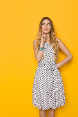 Beautiful young woman in white dotted summer dress is holding finger on chin, looking up and planning. Three quarter length studio shot on yellow background.