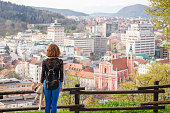 Young woman is looking at the Ljubljana city center and Presern square from Ljubljana castle in Ljubljana, Slovenia