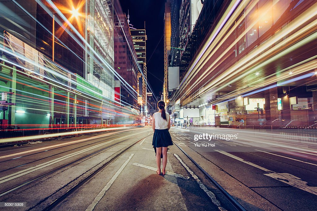 Young woman is lost in metropolitan city at night : Stock Photo