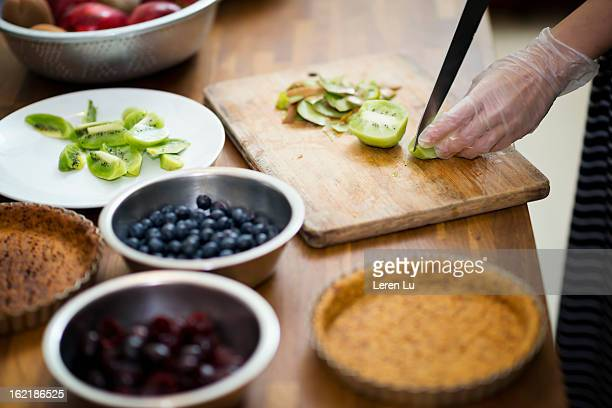 Young woman is making fruit pies
