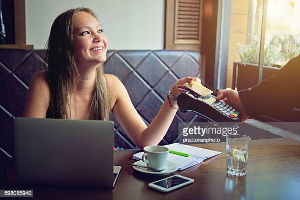 Young woman is paying in the cafe