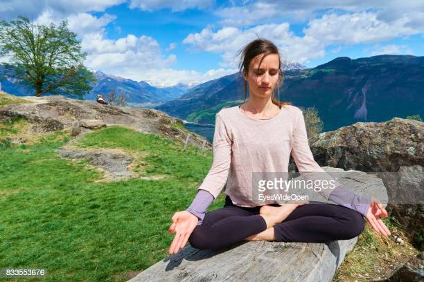 A young woman is practicing openair Yoga and Meditation in lotus position on a rock in the mountains of South Tyrol on April 21 2015 in Lana Italy