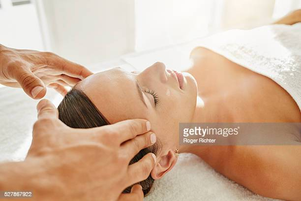 Young woman is receiving a head massage