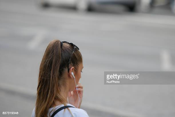 A young woman is seen with headphones at a tram stop on 19 August in Bydgoszcz Poland