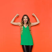 Beautiful young woman in green top is looking at camera, shouting and flexing muscles. Three quarter length studio shot on orange background.