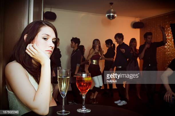 young woman is sitting alone in a nightclub