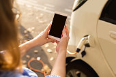 Young woman is standing near the electric car and looks at the smartphone. The rental car is charging at the charging station for electric vehicles. Car sharing.
