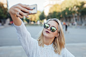 Young woman is taking a selfie by mobile phone. City background