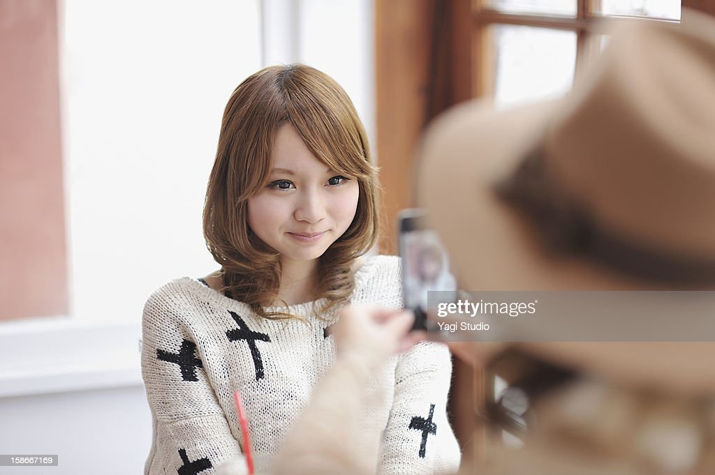 Young woman is taking photos on a smartphone : Stock Photo