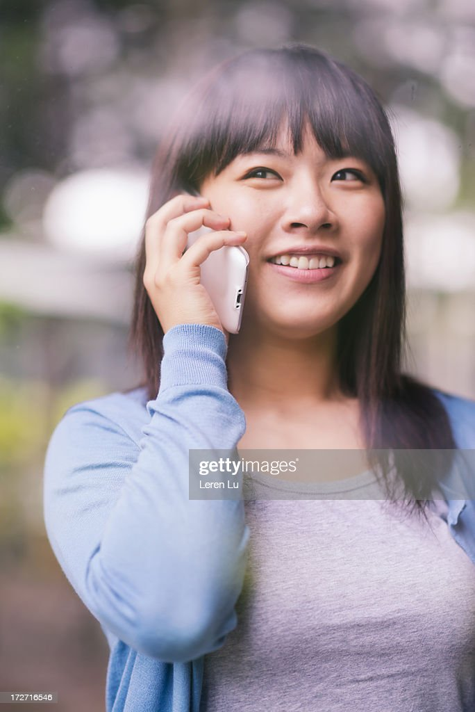 Young woman is talking by smart phone : Stock Photo