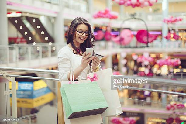 Young woman is texting in a shopping mall
