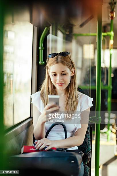 Young woman is texting while commuting