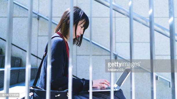Young woman is typing on the steps of stairs