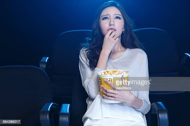 A young woman is watching a movie in the cinema.