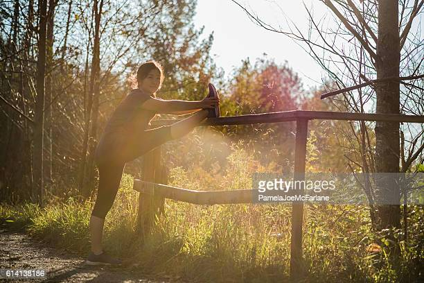 Young Woman Jogger Stretching Leg on Fence on Rural Path