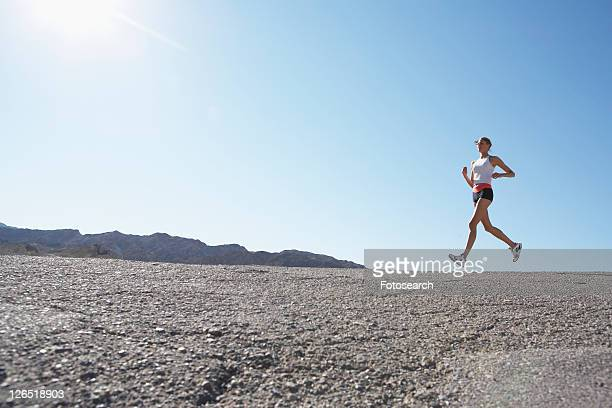 Young woman jogging in rocky landscape (low angle view)