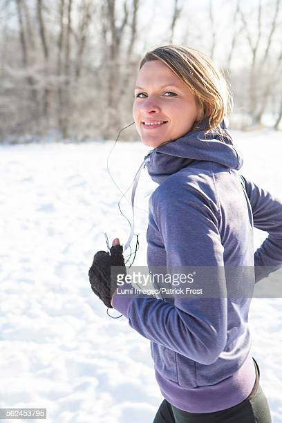 Young woman jogging in snow