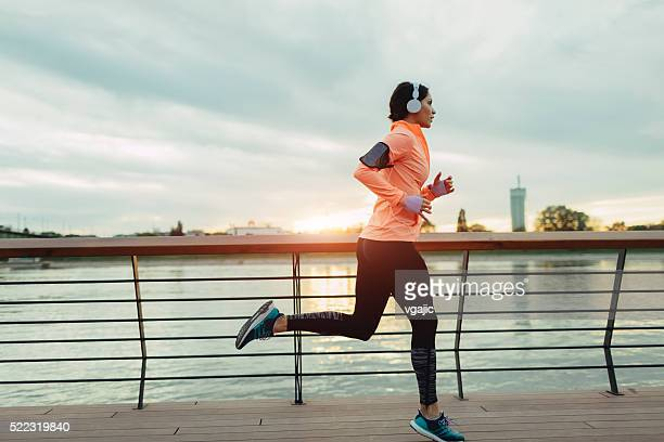 Young Woman Jogging Near River.