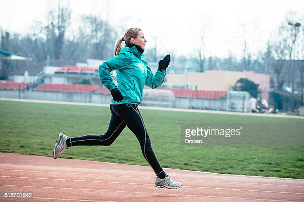 Young woman jogging on athletics lane and living healthy life