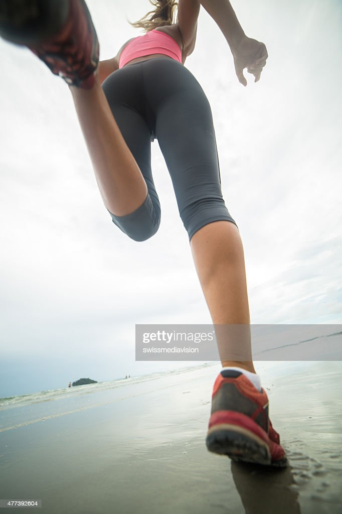 Young woman jogging on beach on cloudy day.Low angle view. : Stock Photo