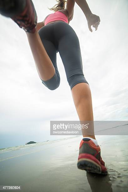 Young woman jogging on beach on cloudy day.Low angle view.