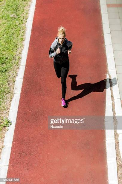 Young woman jogging on running track