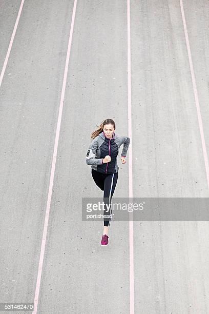 Jeune femme sportive faire du jogging sur la piste