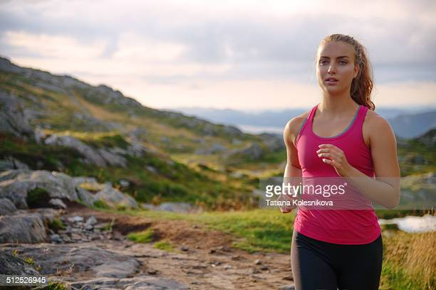 Young woman jogging on top of mountain