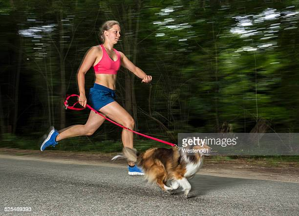 Young woman jogging with dog on road