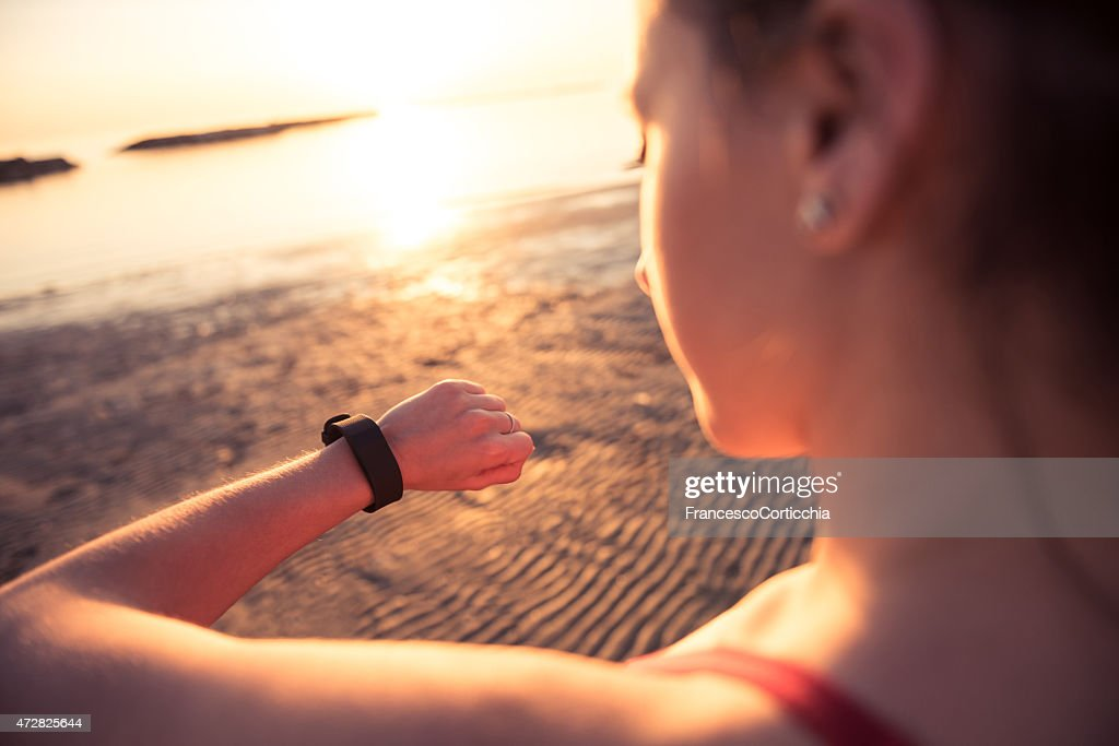 Young woman jogging with heart rate monitor