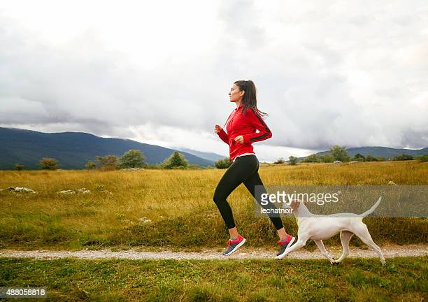 Young woman jogging with her dog
