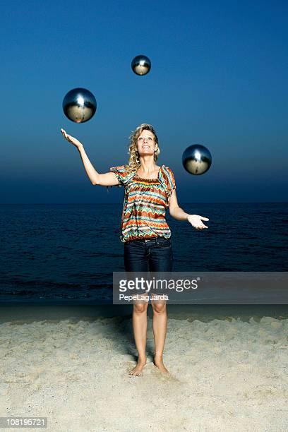 Young Woman Juggling Metal Balls on Beach at Dusk