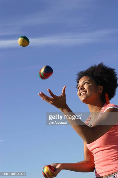 Young woman juggling, side view (blurred motion)