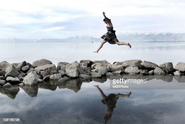 Junge Frau springt über Felsen in Lake