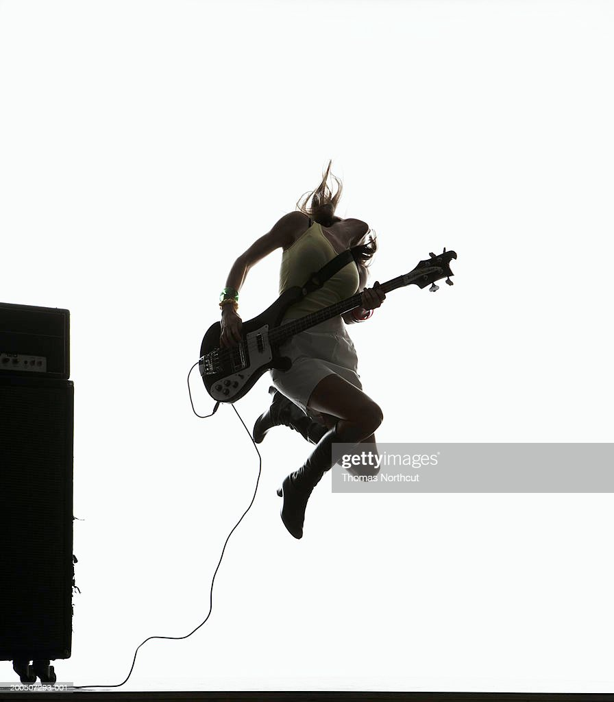 Young woman jumping and playing bass guitar, head back : Stock Photo