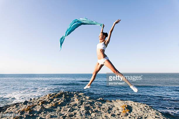 Young woman jumping and waving a blue veil