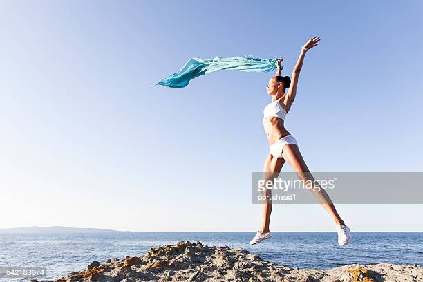 Young woman jumping and waving a sarong
