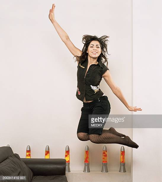 Young woman jumping, arms outstretched, smiling, portrait
