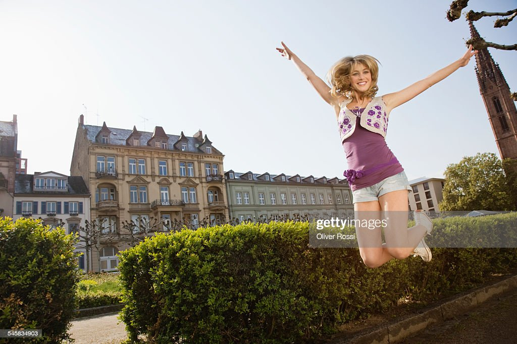 Young woman jumping at university : Bildbanksbilder