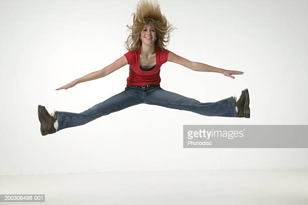 Young woman jumping, doing splits, portrait