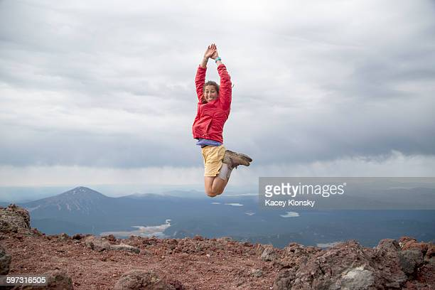 Young woman jumping for joy at the summit of South Sister volcano, Bend, Oregon, USA