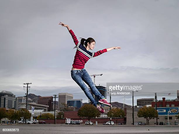 Young woman jumping for joy city in background