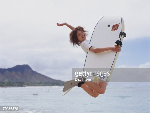 Young woman jumping in air, holding paddleboard : Stock Photo