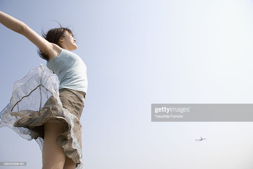 Young woman jumping in air outdoors, arms outstretched : Stock Photo